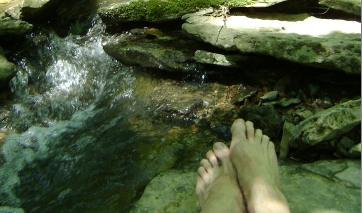 Feet near babbling brook